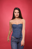 Pretty young woman with slim waist in jean corset. Against the red background Stock Photo
