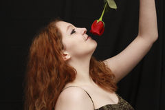 Pretty young woman smelling rose Stock Image