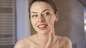 Charming woman spreading cream on face stock video footage