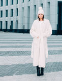 Pretty young woman smiling in a knitted hat and a coat on a background of the Europe city. Royalty Free Stock Photography