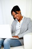 Pretty young woman smiling and looking to laptop Royalty Free Stock Photos
