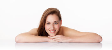 Pretty young woman smiling for pampering massage. Haircare concept - gorgeous 20s woman with long brown hair smiling leaning on clear white glass for massage and Royalty Free Stock Images