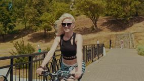 Pretty young woman smiling while riding her bicycle on sunny summer day in slomo stock footage