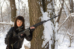 Pretty woman with a sniper rifle. Pretty young woman with a sniper rifle near the tree Stock Image