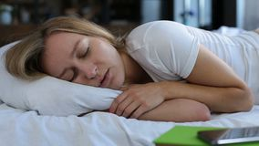 Pretty young woman snoring in bed. Portrait of adorable blonde female with beautiful long hair snoring while sleeping in bed at home. Closeup. Lovely young woman stock video