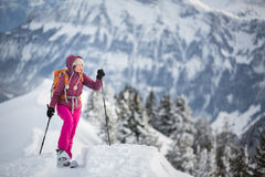 Pretty, young woman snowshoeing in high mountains Royalty Free Stock Photo