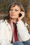 Pretty young woman speaking on the phone. In the park outdoors Stock Images
