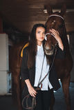 Pretty young woman standing in barn hugging her horse Royalty Free Stock Image