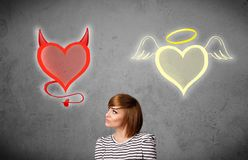 Woman standing between the angel and devil hearts. Pretty young woman standing and deciding between the angel and the devil heart royalty free stock image