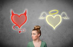 Woman standing between the angel and devil hearts. Pretty young woman standing and deciding between the angel and the devil heart royalty free stock photo