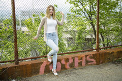 Pretty young woman standing near chain link fence Stock Photos