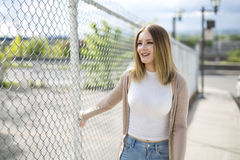Pretty young woman standing near chain link fence Stock Image