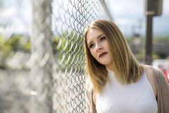 Pretty young woman standing near chain link fence Royalty Free Stock Photography