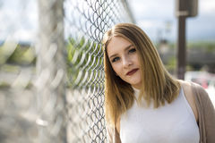 Pretty young woman standing near chain link fence Stock Photography