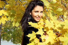 Pretty young woman standing near maple Royalty Free Stock Photo