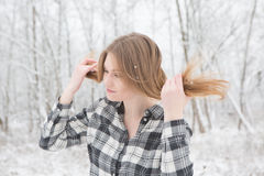 Pretty young woman standing in a winter forest. Young woman in black and white plaid shirt stading in a snow covered forrest Royalty Free Stock Photos