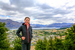 Pretty young woman is staying on the mountain with Panoramic view of lake Wanaka town at the back New Zealand Stock Photo