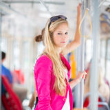 Pretty, young woman on a streetcar/tramway. During her commute to work (color toned image; shallow DOF Royalty Free Stock Photos