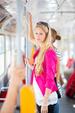 Pretty, young woman on a streetcar/tramway. During her commute to work (color toned image; shallow DOF Stock Image