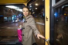 Pretty, young woman on a streetcar/tramway. During her evening commute home from work (color toned image; shallow DOF Royalty Free Stock Image