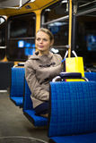Pretty, young woman on a streetcar/tramway. During her evening commute home from work (color toned image; shallow DOF Royalty Free Stock Photos