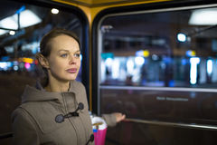 Pretty, young woman on a streetcar/tramway. During her evening commute home from work (color toned image; shallow DOF Royalty Free Stock Photography