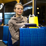 Pretty, young woman on a streetcar/tramway. During her evening commute home from work (color toned image; shallow DOF Royalty Free Stock Images
