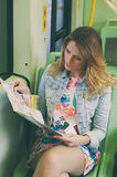 Pretty young woman on a streetcar/tramway looking a map, during Royalty Free Stock Photo