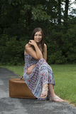 Pretty young woman in sundress sitting with suitcase Royalty Free Stock Photos