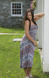 Pretty young woman in sundress standing near porch Stock Photography