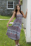 Pretty young woman in sundress standing near porch Stock Photo