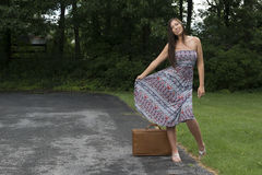 Pretty young woman in sundress standing with suitcase Stock Image