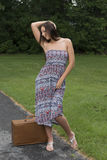 Pretty young woman in sundress standing with suitcase Stock Photo