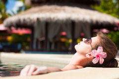 Pretty young woman in sunglasses with flower in hair in luxury pool Royalty Free Stock Photography