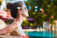 Pretty young woman in sunglasses with flower in hair in luxury pool. Remote tropical beaches and countries. travel concept Royalty Free Stock Images