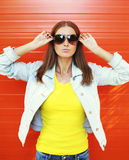 Pretty young woman in sunglasses and jeans jacket over orange Royalty Free Stock Image