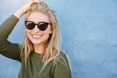 Pretty young woman in sunglasses smiling. Close up shot of pretty young woman in sunglasses smiling. Attractive young female model with copy space on blue stock images