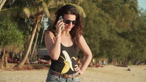 Happy woman makes phone call and talks on beach stock video footage