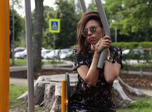 Pretty young woman  in sunglasses. Training apparatus. Pretty young woman  in sunglasses, sitting on training apparatus Royalty Free Stock Image
