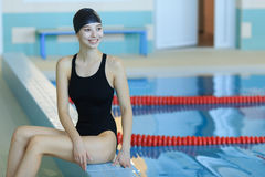Pretty young woman swimmer wearing swim cap at the pool. Stock Photos