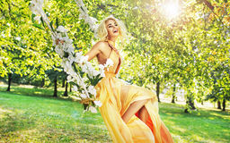 Pretty young woman swinging in the middle of the garden Stock Image