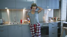 Woman listening to music in kitchen stock video
