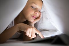 Pretty, young woman with a tablet computer in her bed royalty free stock photos
