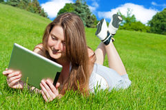 Pretty young woman with tablet lying on grass. Stock Photography