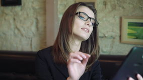 Pretty young woman taking glasses and using tablet in cafe. 4k stock video footage