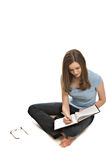 Pretty young woman taking notes. Pretty young woman seated on floor writes in a notebook stock photography