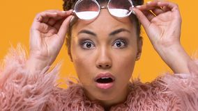 Pretty young woman taking off stylish glasses, looking surprised, shocking news