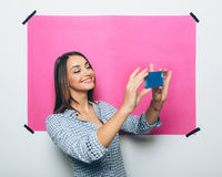 Pretty young woman taking picture with camera phone Stock Images