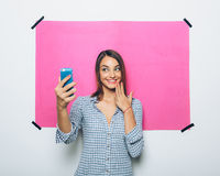 Pretty young woman taking picture with camera phone Royalty Free Stock Image