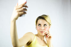 Pretty young woman taking a selfie with a white smartphone. focus on the girl Royalty Free Stock Image